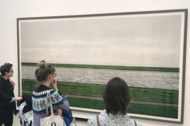 Three spectators gaze at Andreas Gursky photo