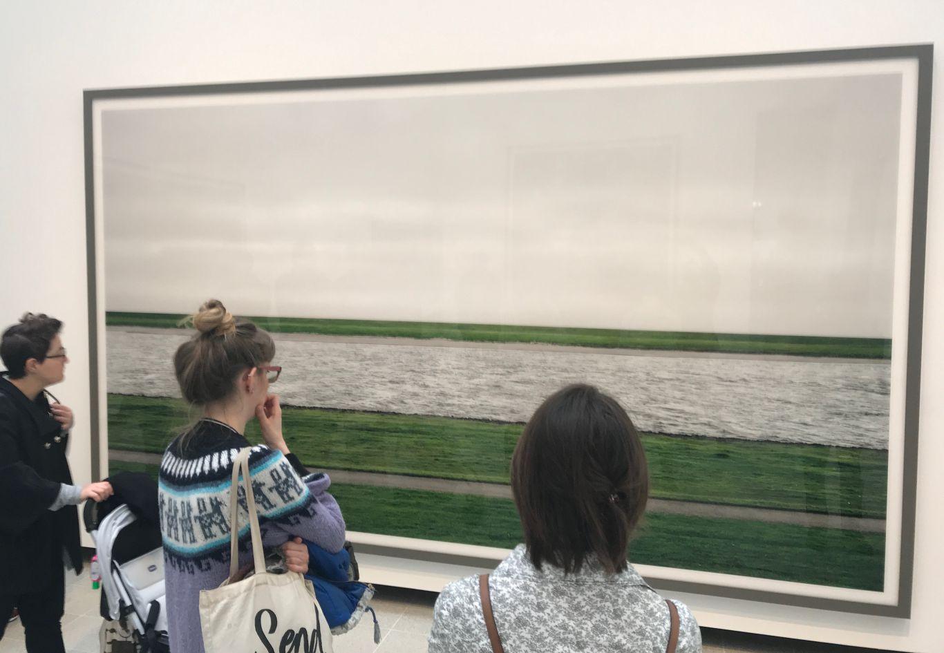Three spectators gaze at Andreas Gursky photo