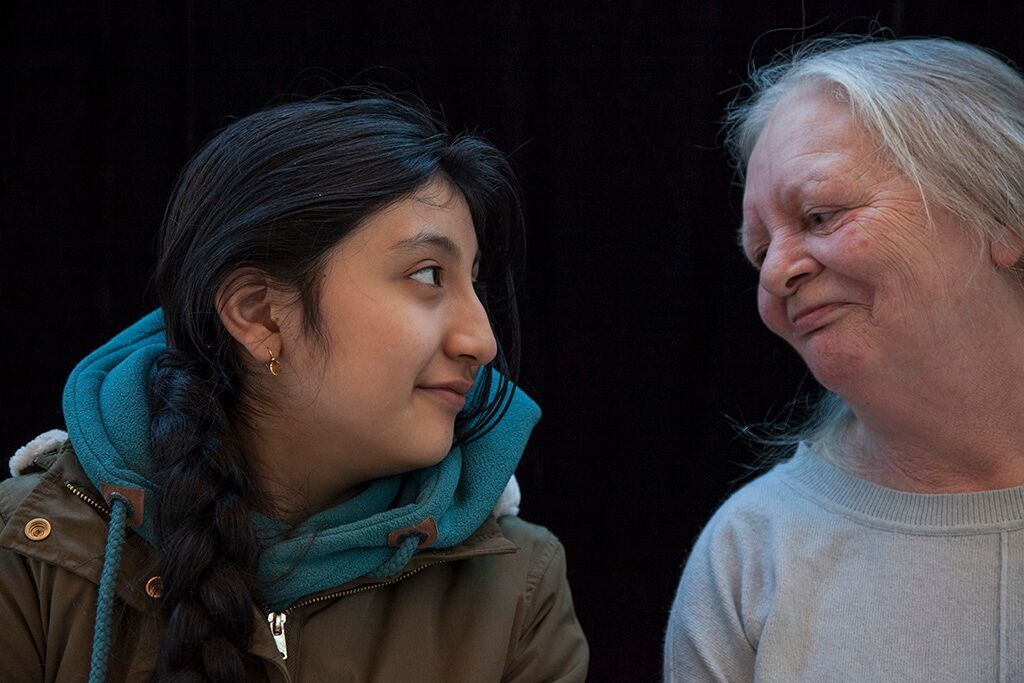 Older woman and young girl gaze at each other