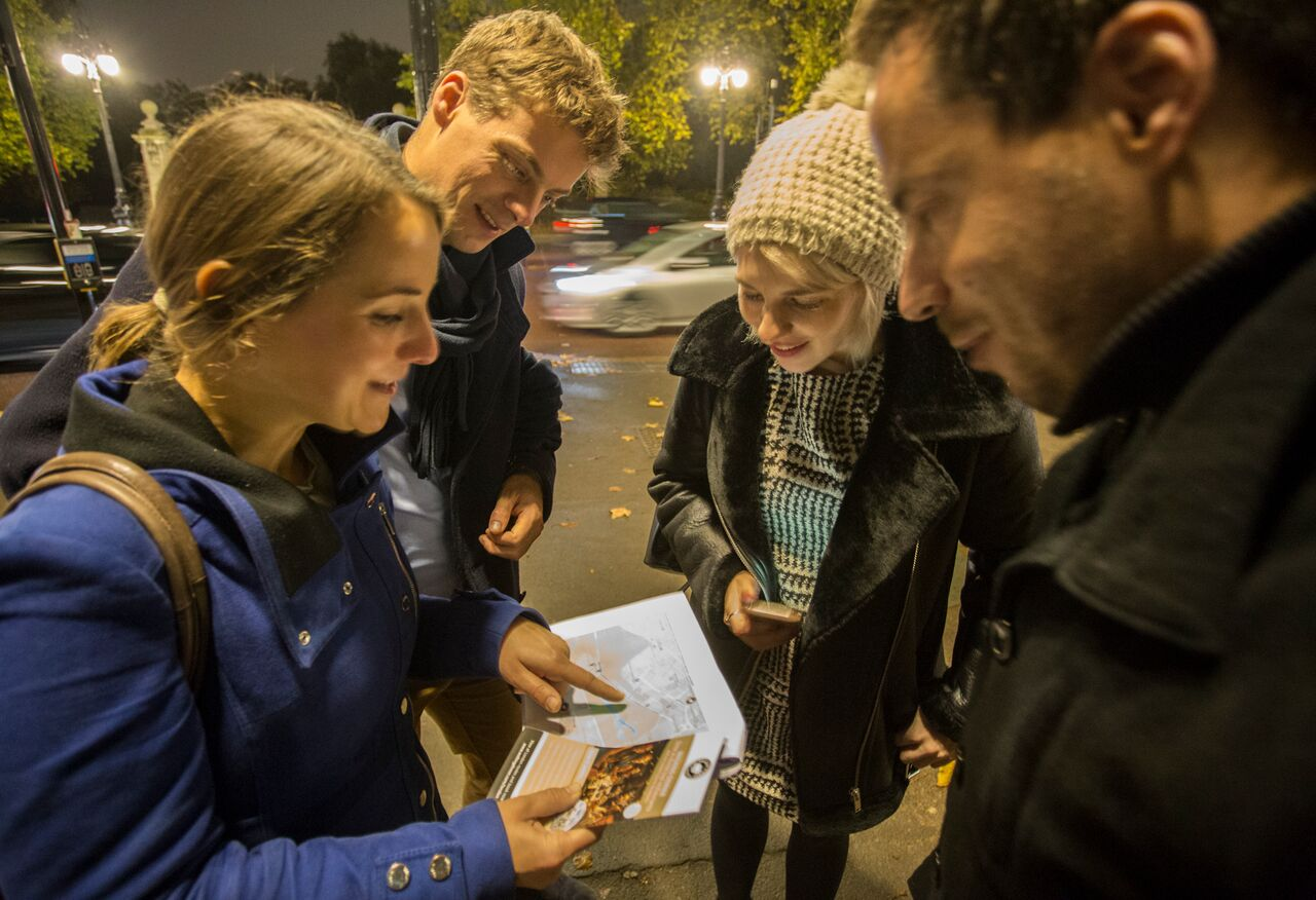 People huddle to look at map on Southbank walking dinner