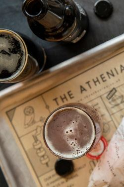 A halloumi wrap and glass of beer on a tray at The Athenian